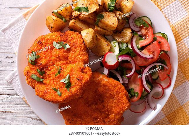 Wiener schnitzel, fried potatoes and vegetable salad on the table close-up. horizontal view from above