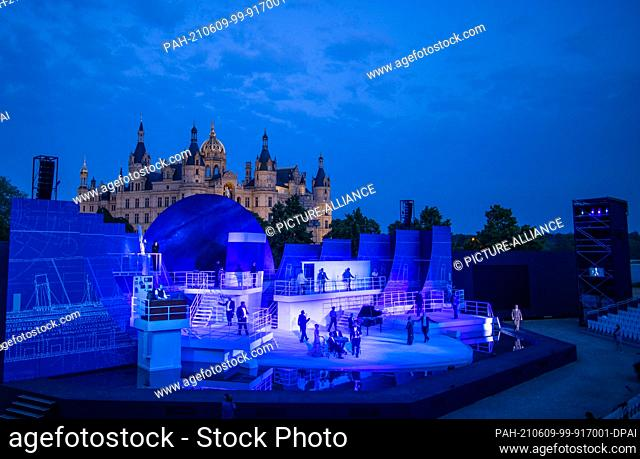 """07 June 2021, Mecklenburg-Western Pomerania, Schwerin: Singers and actors are reflected in a body of water in the musical """"""""Titanic"""""""" on the stage of the..."""