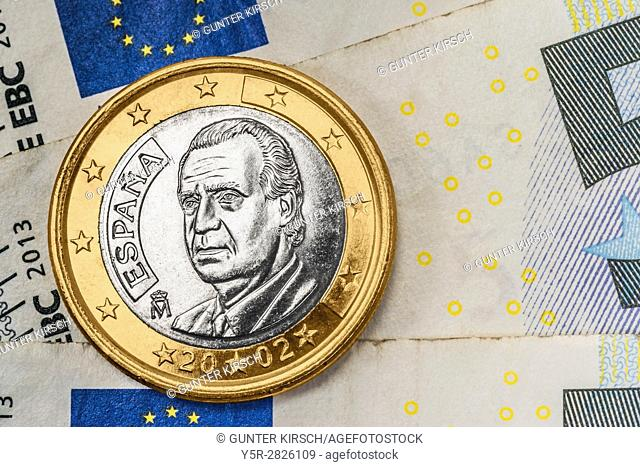 a 1 euro coin from Spain on euro banknotes