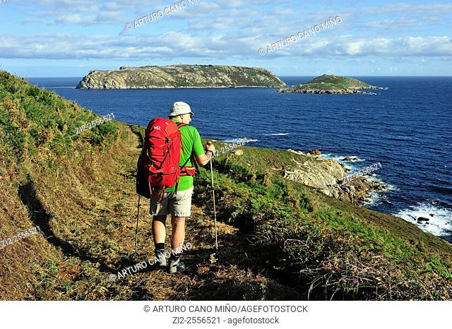 A hiker on the Camiño dos Faros Way of the Lighthouses, in the background they are the islands Sisargas. Malpica de Bergantiños, La Coruña, Spain