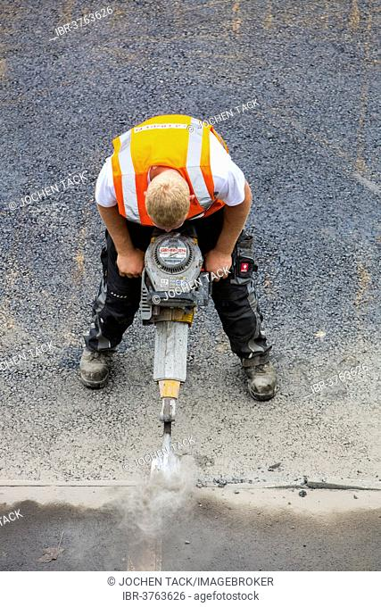 Road construction worker operating a pneumatic drill, tarmac laying works at a road construction site, Essen, North Rhine-Westphalia, Germany