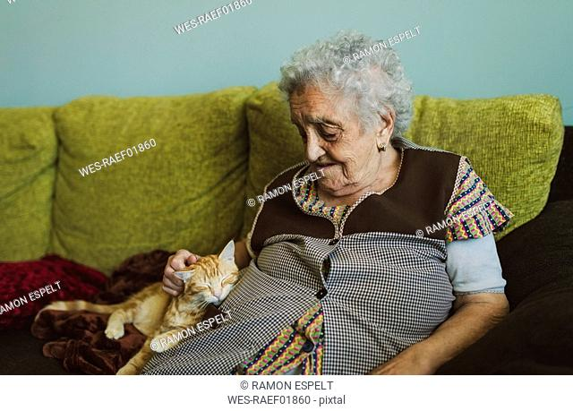 Senior woman sitting on couch stroking tabby cat