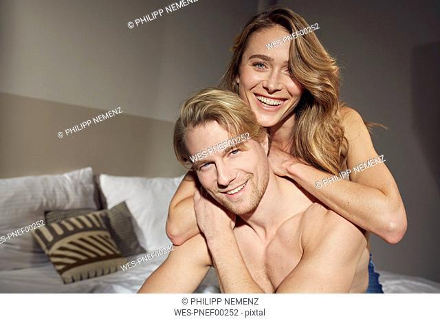 Portrait of happy couple in love in bedroom