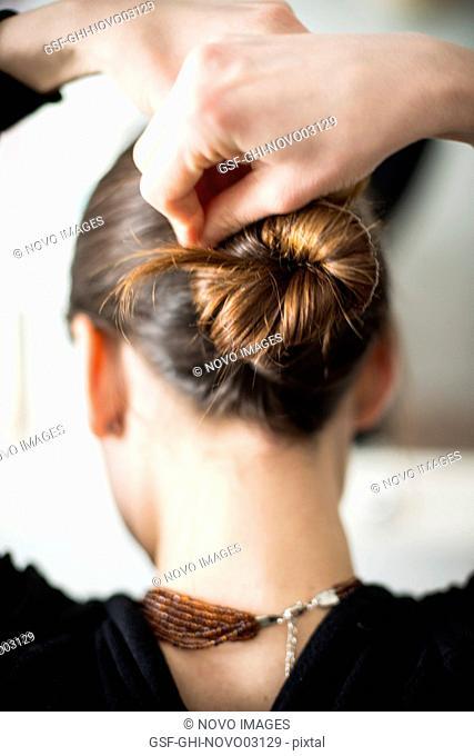 Woman Styling her Hair in Bun, Rear View
