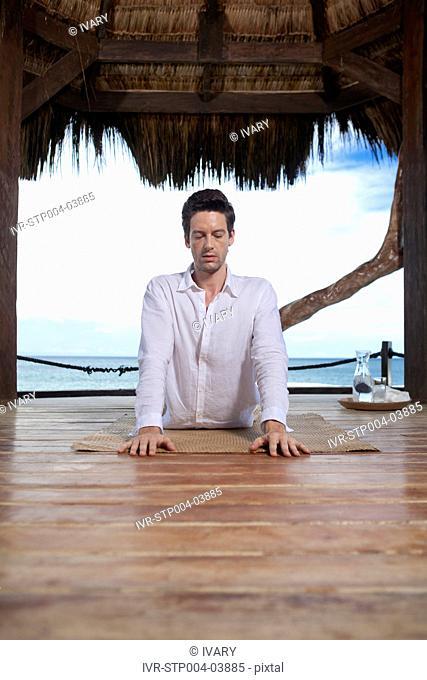 A man doing yoga on a hardwood floor