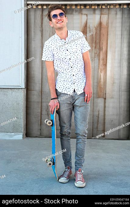 cool street skateboarder with sunglasses in front of iron wall