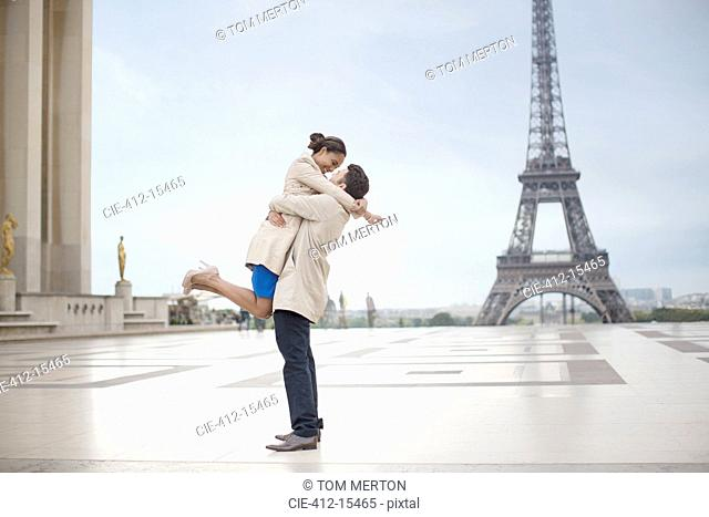 Couple hugging near Eiffel Tower, Paris, France