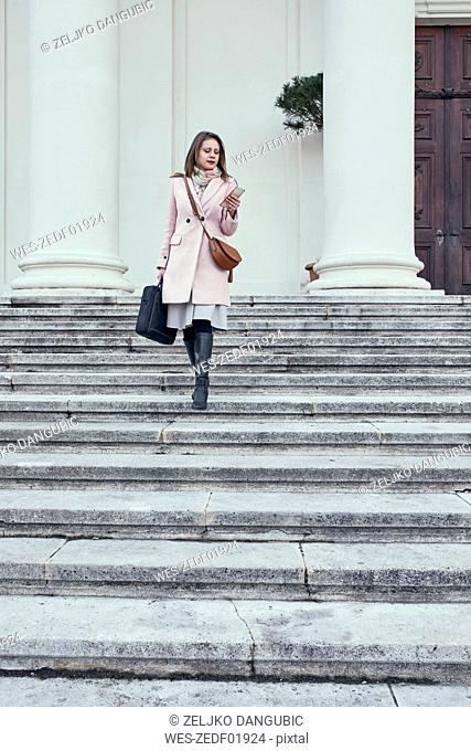 Austria, Vienna, young businesswoman walking downstairs looking at cell phone