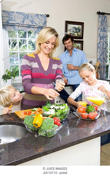Mother making salad by daughter 8-10 pouring juice, father in background