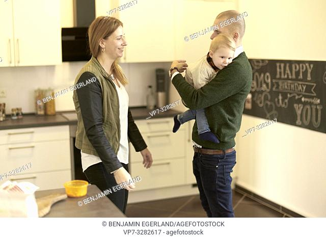 father and mother with baby toddler child at home in kitchen, in Cottbus, Brandenburg, Germany