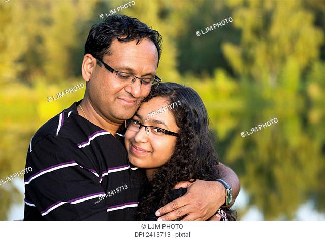 Father and daughter spending quality time together in a park; Edmonton, Alberta, Canada