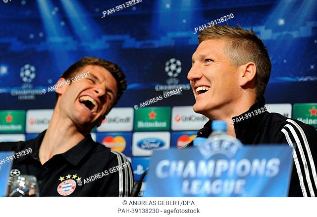 FCBayern Munich's Thomas Mueller (L) and Bastian Schweinsteiger smile during a press conference in Barcelona,Spain, 30 April 2013