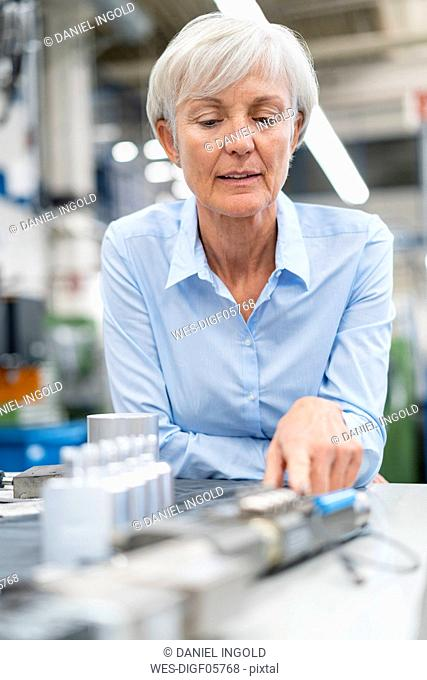 Portrait of senior businesswoman in a factory looking at workpiece