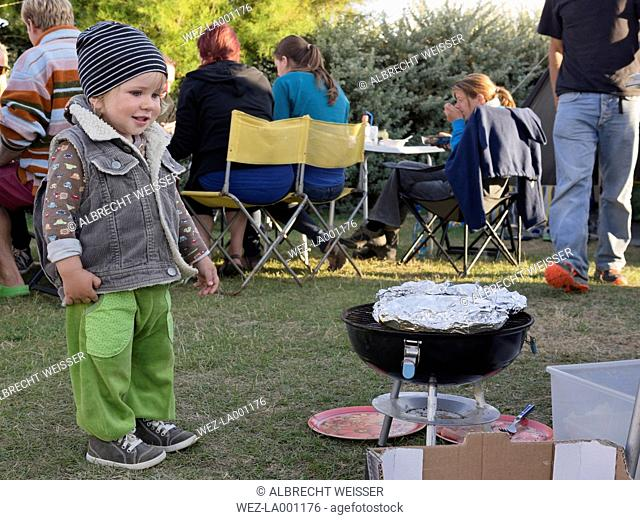 Toddler at a barbecue on a camping ground