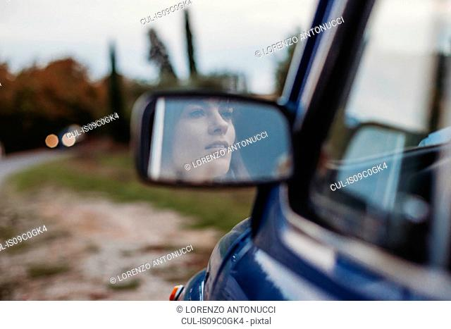 Mirror image of woman driving car