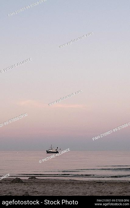 01 September 2021, Schleswig-Holstein, Scharbeutz: A fishing boat sails through Lübeck Bay during the Blue Hour. Photo: Frank Molter/dpa