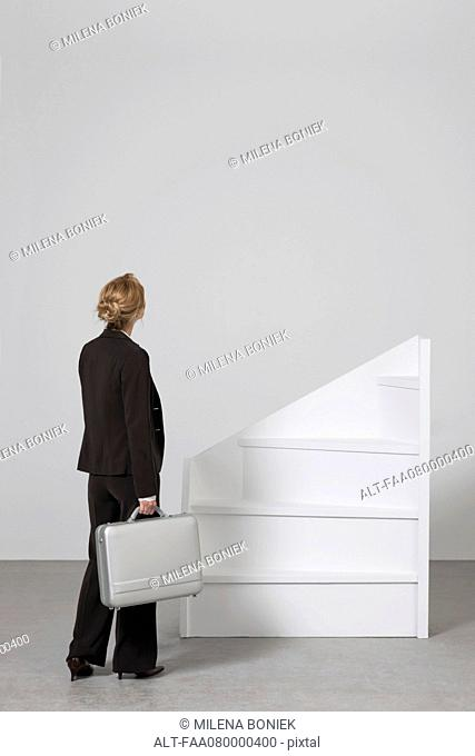 Businesswoman standing before incomplete staircase, rear view