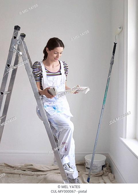 Woman looking at paint color chart