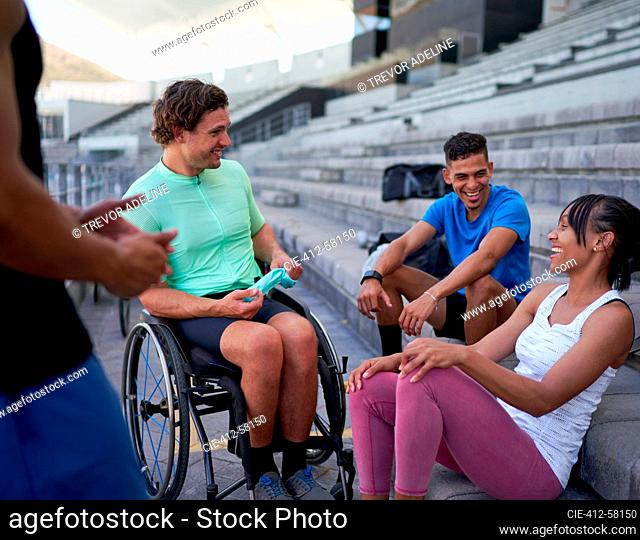 Happy athletes laughing and talking in bleachers