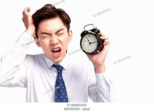 A young business man with an expression of pain holding the alarm clock