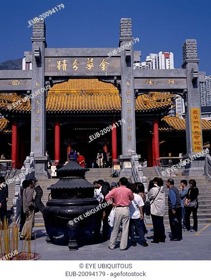 Wong Tai Sin taoist temple established in 1921. Visitors gathered beside incense burner at foot of flight of steps to entrance built in traditional Chinese...