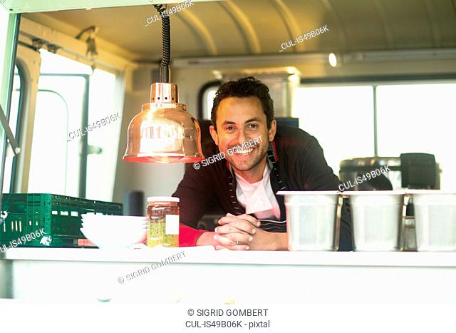 Portrait of small business owner at van food stall hatch
