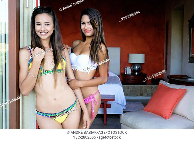 Two attractive young hispanic women in bikini smiling at camera while looking out of their hotel room