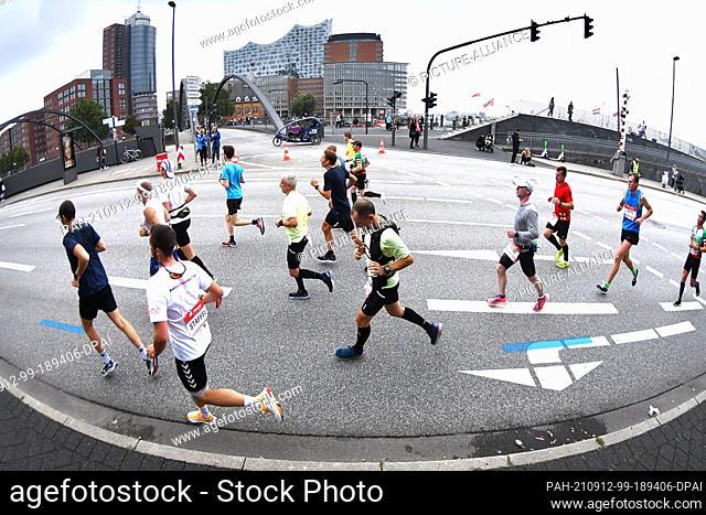 12 September 2021, Hamburg: Athletics: Marathon: Marathon runners in front of Speicherstadt and Elbphilharmonie. Photo: Michael Schwartz/dpa
