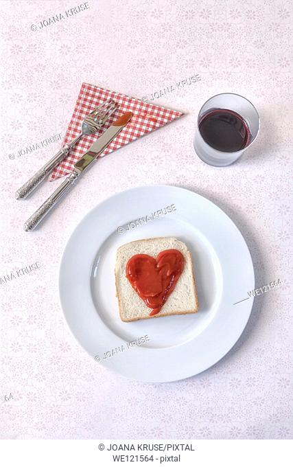 a slice of toast with a heart of ketchup