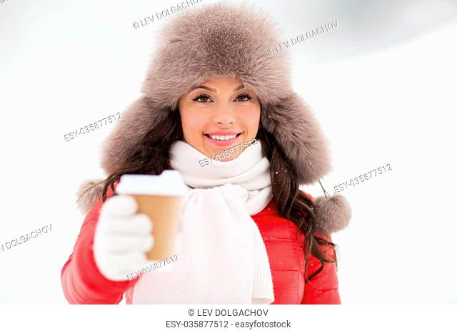 people, hot drinks and leisure concept - happy woman in winter fur with coffee cup hat outdoors