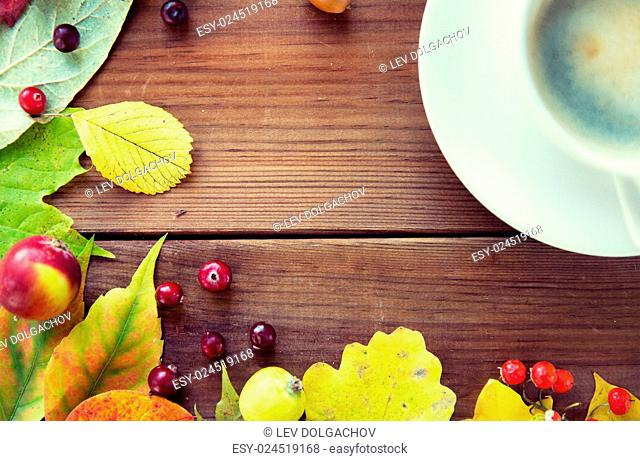 season, drink and morning concept - close up of coffee cup on wooden table with autumn leaves