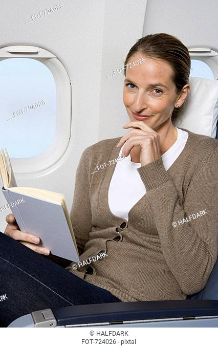 A female passenger reading on a plane
