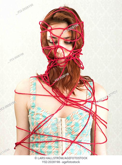 Conceptual image of woman trapped and constrained with red cotton yarn