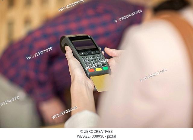 Woman in shop paying with credit card