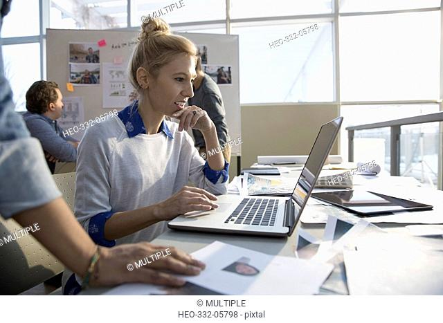 Creative female designer working at laptop in office