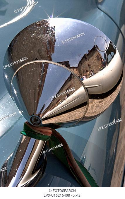 Detail of rear view wing mirror on antique car, with reflection of Italian piazza