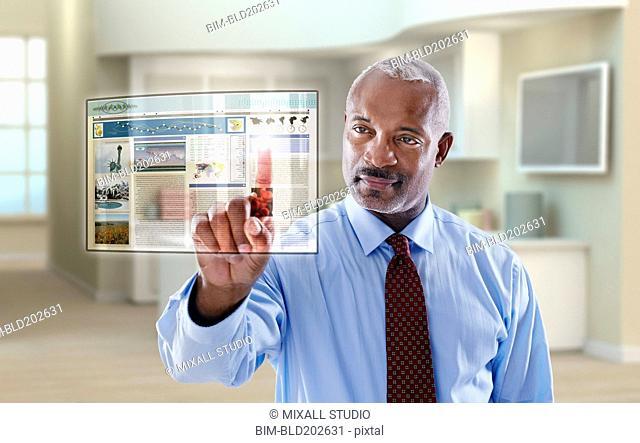 Black businessman using digital display in office