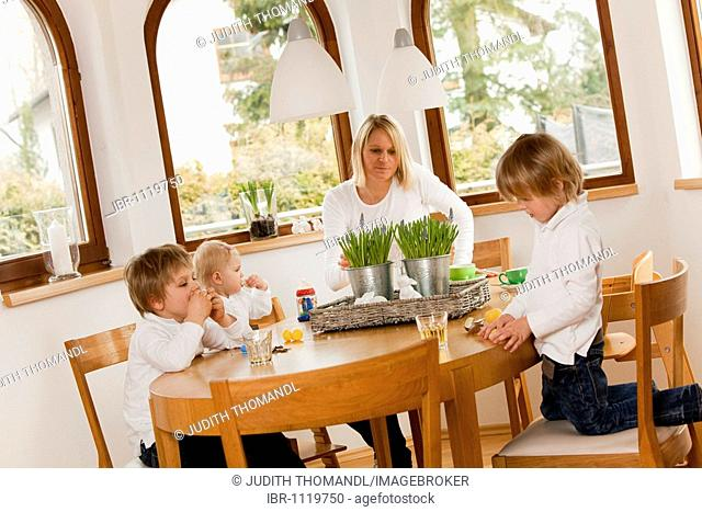 Mother and three children, 1, 3 and 6 years old, sitting at the table and eating sweets