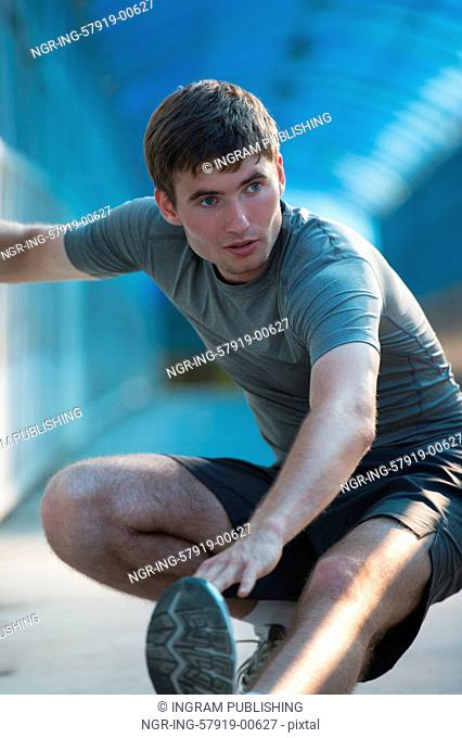 Attractive fit young man stretching before exercise, sunrise early morning backlit. Shallow depth of field
