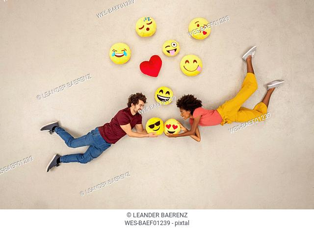 Happy couple, falling in love with emojies over their heads