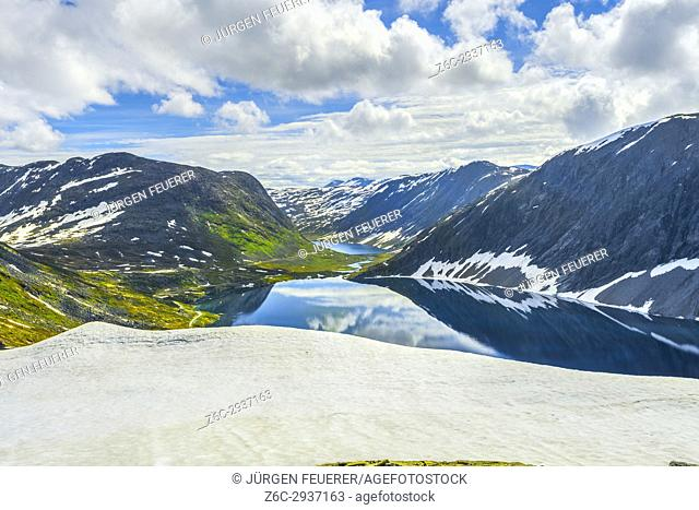 mountain lake Djupvatnet with snowfield, below mountain Dalsnibba near Geirangerfjorden, Norway
