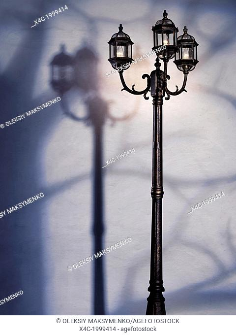 Artistic dramatic photo of a street lamp at night with tree shadow over a white wall