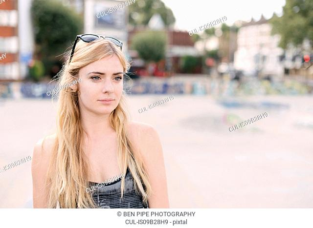 Portrait of young female skateboarder with long blond hair in skatepark