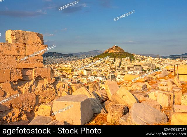Greece. Sunset in Athens. Marble ruins in the foreground. View from a high point on city rooftops and Lycabettus hill