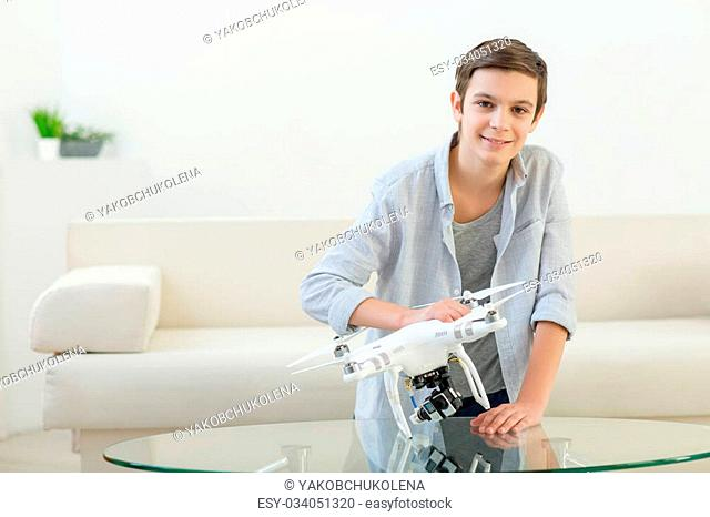 Portrait of pretty boy making fun with a small drone. He is standing at home and smiling. The child is looking at camera happily