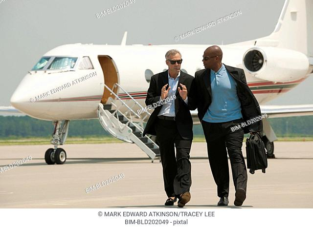 Businessmen walking on airport tarmac