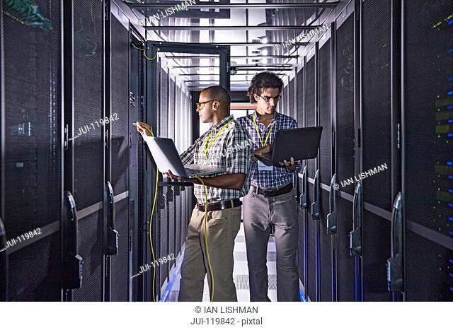 Technicians with laptop working at mainframe computers in data center server farm