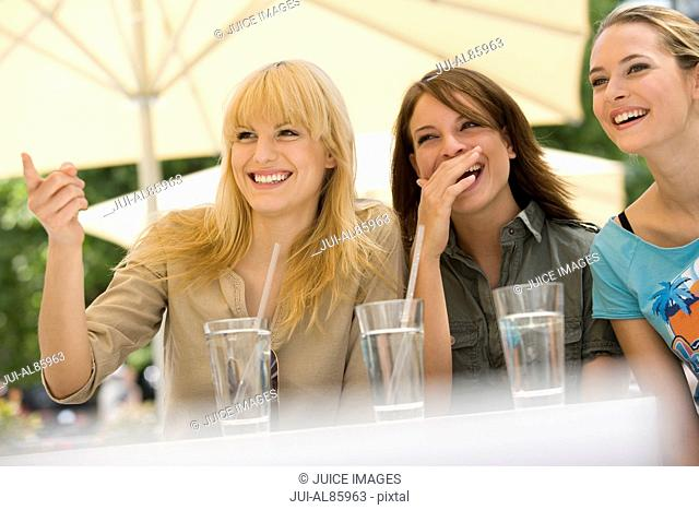 Three women laughing outdoors