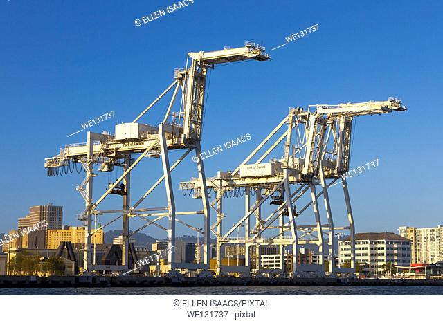 Three giant container cranes looming over the water at the Port of Oakland intermodal container terminal