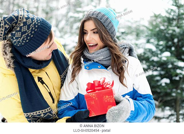 Man giving red gift his girlfriend in winter time. Debica, Poland